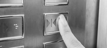 Doigt de femme sur le bouton de l'ascenseur