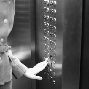 Femme appuyant sur le bouton de l'ascenseur